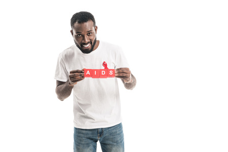 smiling african american man in blank white t-shirt with aids awareness red ribbon and blocks with AIDS lettering isolated on white