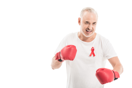 emotional mature man in blank white t-shirt with aids awareness red ribbon and boxing gloves isolated on white, fighting aids concept