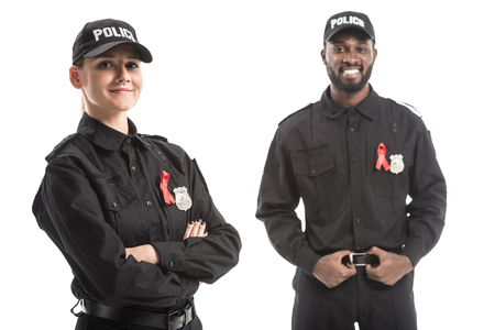 happy police officers with aids awareness red ribbons looking at camera isolated on white