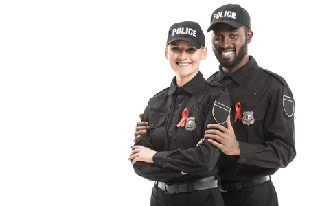 smiling police officers with aids awareness red ribbons looking at camera isolated on white