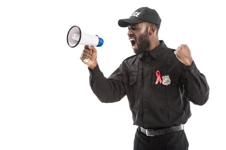 angry african american police officer with aids awareness red ribbon shouting with megaphone isolated on white