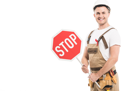 smiling adult builder with aids awareness red ribbon on overall holding stop road sign and looking at camera isolated on white Фото со стока