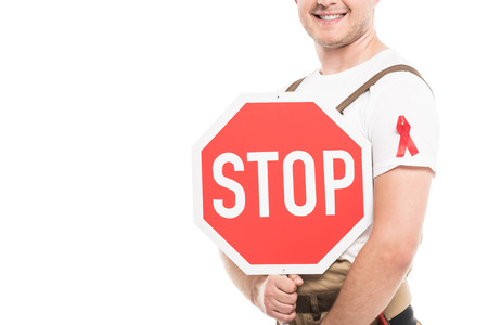 cropped shot of smiling builder with aids awareness red ribbon on overall holding stop road sign isolated on white Stock Photo