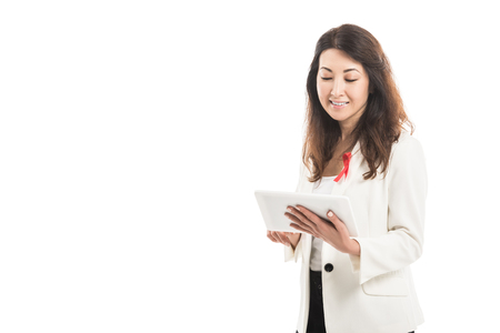 smiling asian businesswoman with aids awareness red ribbon on jacket using tablet isolated on white