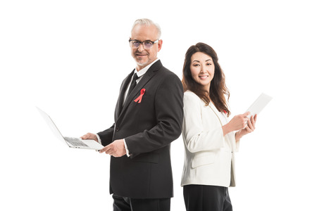 smiling adult businesspeople with aids awareness red ribbons working with gadgets while standing back to back and looking at camera isolated on white
