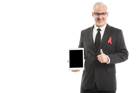 mature businessman in suit with aids awareness red ribbon holding tablet with blank screen and showing thumb up isolated on white