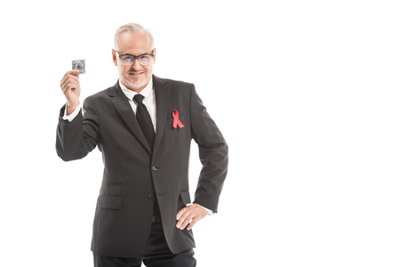 mature businessman in suit with aids awareness red ribbon isolated on white