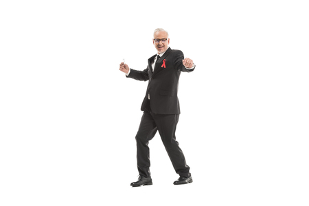 funny mature businessman in suit with aids awareness red ribbon dancing isolated on white Archivio Fotografico