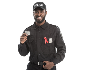 smiling african american police officer with aids awareness red ribbon holding condom isolated on white Reklamní fotografie - 110379594