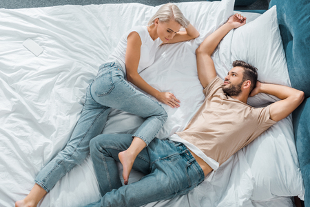 top view of happy young couple relaxing together in bedroom