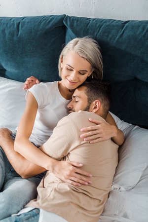 high angle view of happy young couple hugging on bed in bedroom