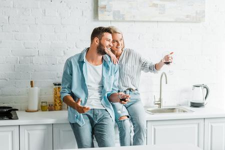 Novia sonriente sosteniendo una copa de vino y apuntando algo a su novio en la cocina