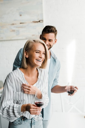young couple holding glasses of wine and laughing in kitchen