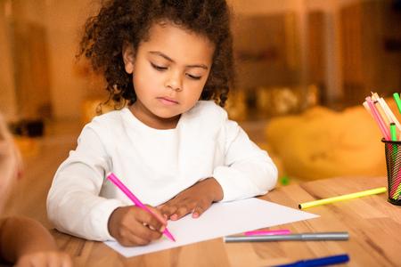 Adorable African American kid drawing with pink felt pen in kindergarten Stockfoto