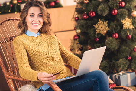 Smiling woman shopping online with credit card and laptop at home with Christmas tree