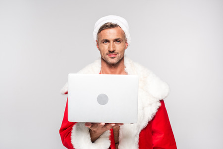 Handsome man in Santa costume holding laptop and smiling at camera isolated on grey