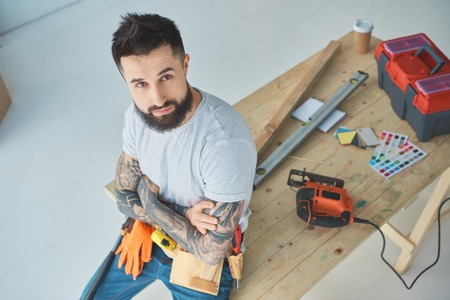 High angle view of bearded repairman with tattoos leaning on wooden table with equipment Stock Photo