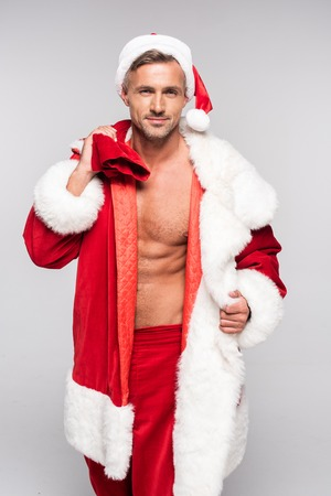 Handsome man in Santa costume holding bag with presents and looking at camera isolated on grey background Stock Photo