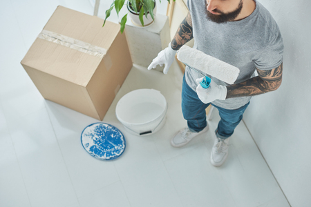 Overhead view of repairman with roll paint brush in new apartment