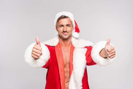 Handsome happy man in Santa costume showing thumbs up and smiling at camera isolated on grey background Stock Photo