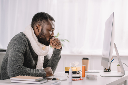 Kranker afroamerikanischer Geschäftsmann hustet am Arbeitsplatz mit Medikamenten