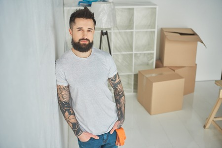 Handsome bearded tattooed man leaning at wall and looking at camera at new home