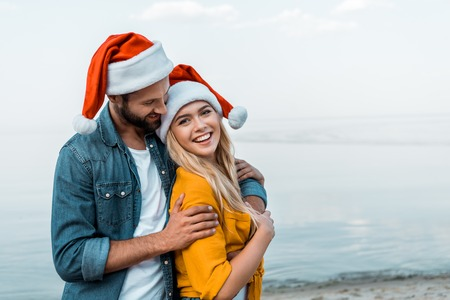 Smiling boyfriend in Santa hat hugging girlfriend on beach Stock fotó