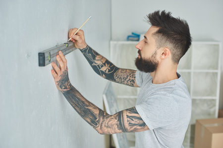 Side view of tattooed young man holding level tool and marking wall with pencil during repairs 写真素材