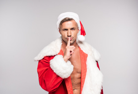 Handsome man in Santa costume holding finger on lips and gesturing for silence isolated on grey background