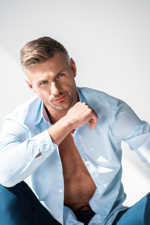 Handsome sexy man with unbuttoned shirt looking at camera isolated on white background