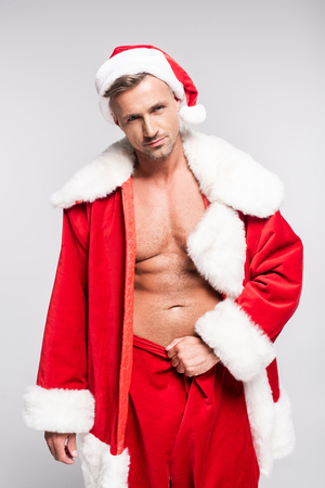 Handsome muscular man in Santa costume looking at camera isolated on grey background Stock Photo