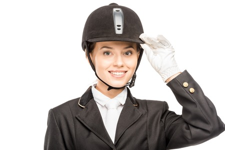Close-up portrait of smiling young horsewoman in safety helmet looking at camera isolated on white background Banco de Imagens