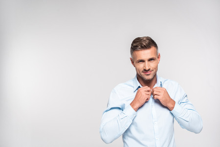 Handsome adult man buttoning shirt isolated on white background