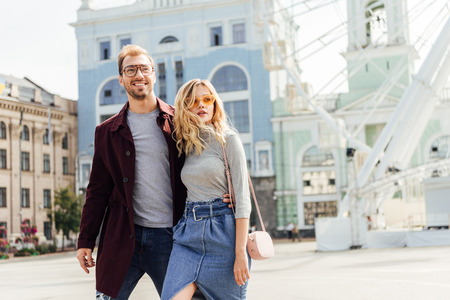 Romantic couple in autumn outfit hugging and walking in city Stock Photo