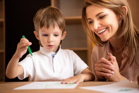 Smiling educator looking at boy drawing in kindergarten
