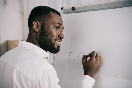 Sonriendo apuesto empresario afroamericano dibujando en el rotafolio en la oficina y mirando a otro lado Foto de archivo