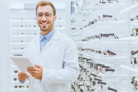 Professional smiling optometrist using digital tablet near eyeglasses on shelves in ophthalmic shop