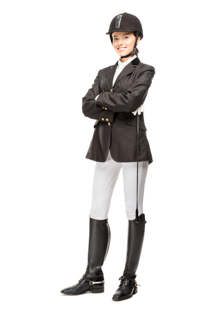 Happy young horsewoman in uniform holding horseman stick and looking at camera isolated on white background