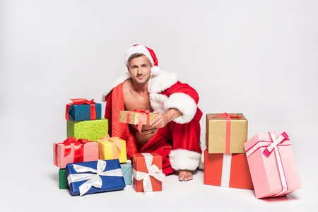 Sexy man in Santa costume sitting with gift boxes and smiling at camera on grey background