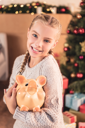 Adorable smiling kid holding piggy bank at home with Christmas tree Stock Photo