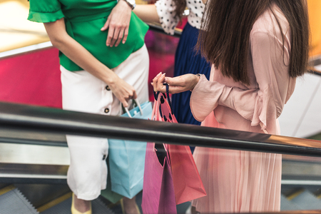 Cropped shot of girls with paper bags standing on escalator in shopping mall