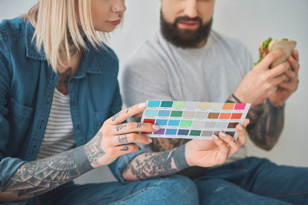 Cropped shot of girl holding color palette and man eating sandwich in new house