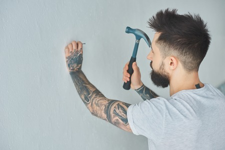 Bearded tattooed young man hammering nail at wall