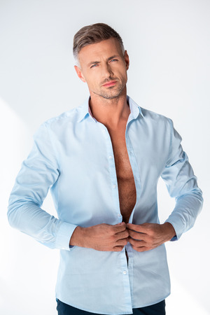 Sexy macho buttoning shirt and looking at camera isolated on white background Stock Photo