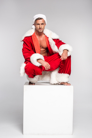 Handsome man in Santa costume crouching on white cube and looking at camera on grey background
