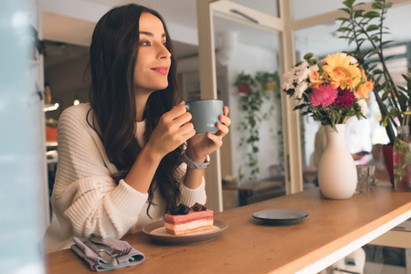 Pensive young woman with coffee cup sitting at table with cheesecake in cafe Stock fotó