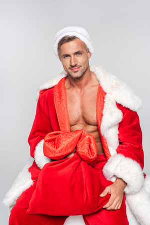 Handsome man in Santa costume holding red bag and smiling at camera isolated on grey background