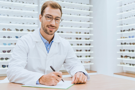 Professional optometrist writing diagnosis in ophthalmic shop