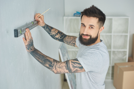 Handsome bearded young man holding level tool and smiling at camera during home improvement Reklamní fotografie