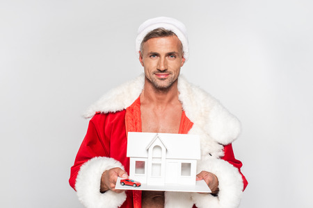 Handsome smiling man in Santa costume holding house model with small red car isolated on grey background Stock Photo